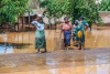 Women standing on a flooded street in Tanzania.